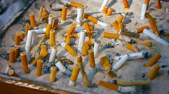 Cigarette butts in a designated smoking area Stock Footage