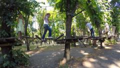 Two boys and two girls played on the logs suspended in extreme park. - stock footage