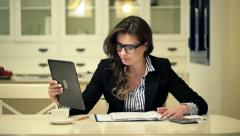 Young businesswoman with documents during video chat on tablet computer at home Stock Footage