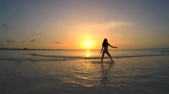 Young Asian Chinese girl in swimwear on sunset ocean beach Stock Footage