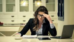 Tired businesswoman having headache during work with documents at home at night - stock footage