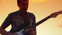 Male guitarist playing rock in the sunset on a warm summer night Stock Footage