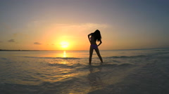 Young ethnic female in bikini dancing on the beach at sunset Stock Footage