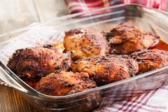 Roasted chicken drumsticks in casserole dish. Selective focus Stock Photos