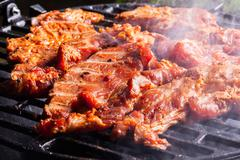 Grilling pork steaks on barbecue grill. Selective focus Stock Photos