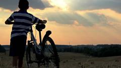 Boy with the bicycle in the field at sunset, teenager Stock Footage
