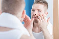Male narcissus examining complexion Stock Photos