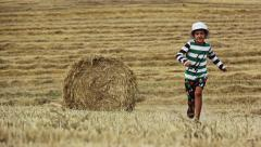 Boy running in a field near the haystack, mown field and boy Stock Footage