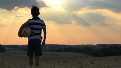 Stock Video Footage of boy with a ball in a field at sunset, boy dreams of becoming a soccer player