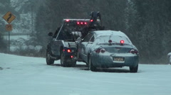 Car in Snow Storm About to be Towed by Truck Stock Footage