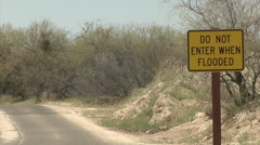 Car Driving Past Sign Warning of Desert Fash Flood Hazard Stock Footage