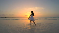 Beautiful Asian Chinese girl in white dress on ocean beach Stock Footage