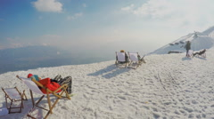 Tourists enjoying view from top of snowy mountain, having rest in chairs, relax Stock Footage