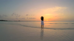Young ethnic female in white sundress dancing on beach at sunset Stock Footage