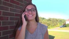 Teenage Girl Talks on Cellphone Outside Home - stock footage