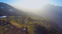 Aerial shot of small farming village on green hill of mountain in rays of sunset Stock Footage