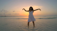 Young Asian Chinese girl in white on ocean beach at sunrise Stock Footage