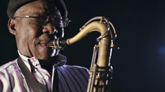 African man colored old black playing saxophone dark background music face Stock Footage