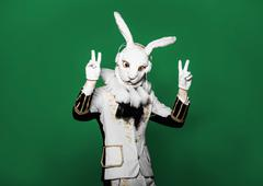 Actor posing in white rabbit suit with earphones on  green background.Studio - stock photo