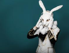 Actor posing in white rabbit suit with earphones on  blue background.Studio shot - stock photo