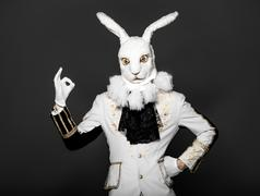 Actor posing in white rabbit suit on black background.Studio shot.Halloween time - stock photo