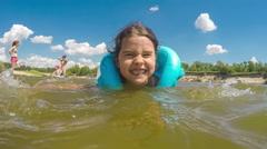 The girl child is learning to swim in the river lifejacket summer blue sky Stock Footage