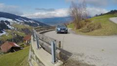 Car driving on serpentine road in mountains, cottages on green slopes, landscape Stock Footage