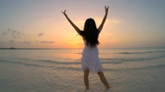 Barefoot Asian Chinese girl in white dress dancing on beach - stock footage
