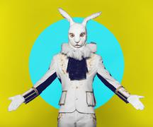 Actor posing in white rabbit suit on color yellow blue background.Studio shot - stock photo
