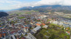 Aerial panorama of modern town in green Alpine valley, beautiful mountain nature Stock Footage