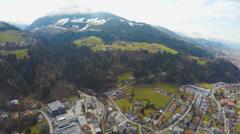 Aerial shot of big city, beautiful Alps around it, green downhills, snowy peaks Stock Footage