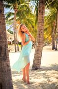 Stock Photo of blonde girl in azure on tiptoe with hand on head among palms