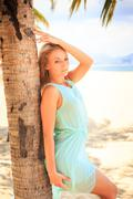 blonde girl in transparent frock leans on palm trunk - stock photo
