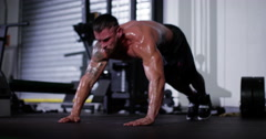 An athlete doing extreme push ups at a gym. Shot on RED Epic. Stock Footage