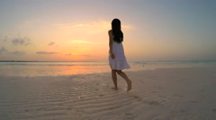 Young ethnic female in white sundress dancing on beach Stock Footage