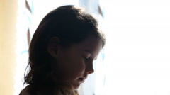 Girl child prays standing at the window silhouette Video childhood religion - stock footage