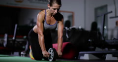 A fit woman works out in her home gym with an ab roller. Shot on RED Epic. Stock Footage
