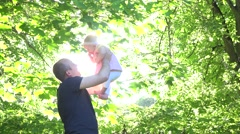 Father lifting happy baby girl under tulip tree in front of sunlight. 4K Stock Footage