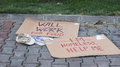 Beggar banners and money in cap Stock Footage