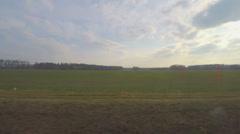 Train passing vast farming fields, plants, industrial area, view through window Stock Footage