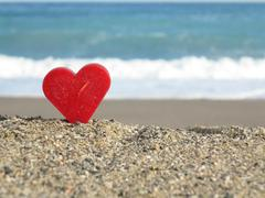 Red heart on white sand beach Stock Photos