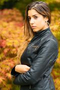 Portrait of beautiful young girl with a background of autumn leaves - stock photo