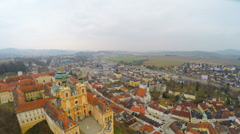 Aerial shot of old European city on river bank, gray sky, mountains on horizon Stock Footage
