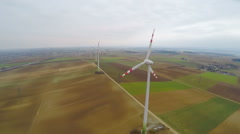 Stock Video Footage of Wind turbines rotating on green field. Alternative source of energy. Aerial view
