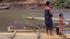 Mom with a child standing on bamboo raft in Inle Lake Burma Stock Footage