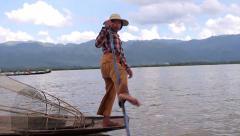Fisherman rowing of leg on sampan boat Burma Myanmar Stock Footage