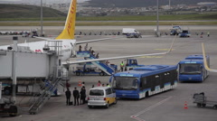 Passengers get off airplane into buses at airport Stock Footage
