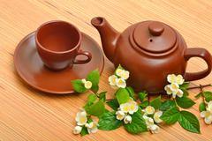 Clay teapot, teacup, saucer and jasmine flower twig on wood - stock photo