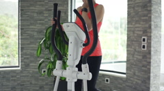 Woman exercising on elliptical machine talking on cellphone, slow motion, 240fps Stock Footage