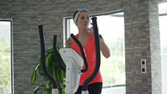 Woman drinking water during exercise on elliptical machine in gym Stock Footage
